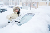 Fototapety Woman scraping snow off of windshield