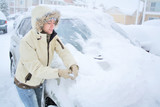Woman removing snow from windshield poster