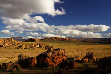 Yellow red desert cliffs and stones against cloudy sky