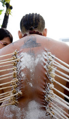 a devotee of thaipusam with hooks piercing backs