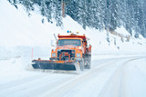 Snow plow removing snow from mountain highway poster
