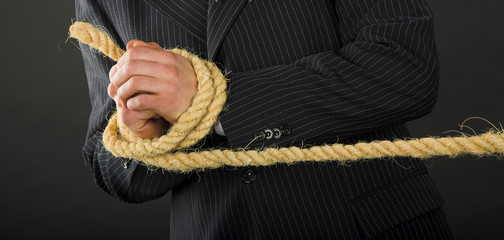 businessman hands with rope isolated on the black