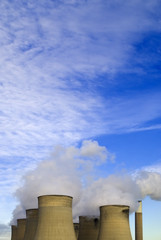 Cooling towers under blue sky with clouds