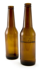 Two Beer Bottles, One Half Empty Isolated on White Background.