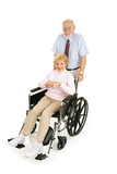 Senior man pushing his wife in wheelchair.  Full body isolated poster