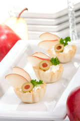 Three mini fillo shells filled with cream cheese, pears, olives