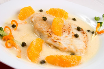 Closeup of grilled skate (ray) with orange and caper sauce