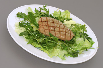 Griddled steak served on a fresh green rocket and iceberg salad