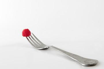 single raspberry on fork