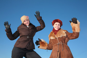 two young woman posing agains blue sky in winter