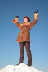 pretty young woman stand on snow hill with hands up