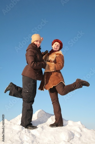 two young woman posing on snow hill