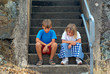 brother and sister sit on the steps