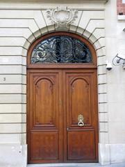 Porte cochère marron sur façade de pierre, Paris, France