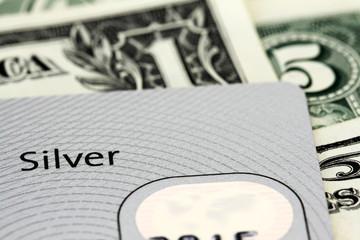 Silver credit card on dollar bills