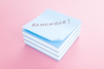 Pile of sticky notes with text over a pink table