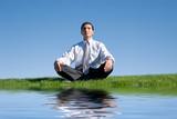 Businessman meditating on green grass poster
