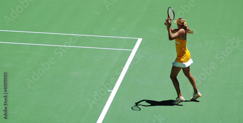 a girl in tennis action.  Yellow dress and green tennis field