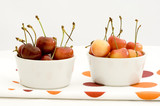 Two bowls of cherries on colourful napkin poster