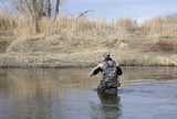 Hunter (trapper) in camouflage cloths crossing a shallow river poster