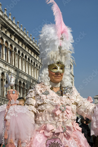 Woman wearing a pink Venetian disguise with hat of plumes