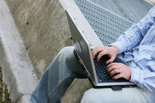 young man sitting while typing on laptop