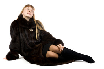 Pretty young girl in black fur jacket. Isolate on white.