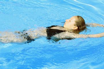 Frau schwimmt im Freibad in der Sonne