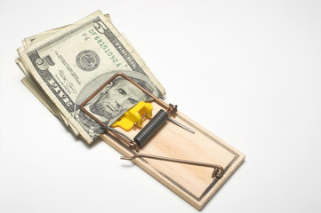 Money trapped in a mousetrap. Financial concept.