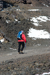 Hiker with poles walking the stony trail on the volcano Etna