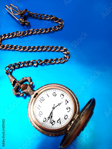 close-up of old golden clock on blue background