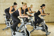 The group of women training on exercise bikes at the gym.