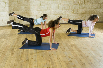 A group of women making stretching exercise on yoga mat.
