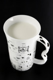White cup of milk on black  (small depth of sharpness) poster