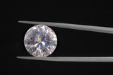 Diamond held by a gem tweezer shot on black poster