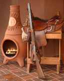 Saddle, rifle and kiva fireplace still life depicting New Mexico poster