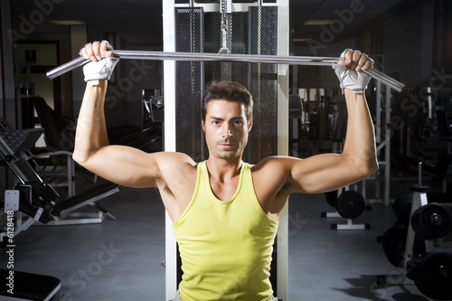 health club: man in a gym doing weight lifting.