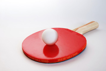 Red ping-pong paddle with the ball isolated on white