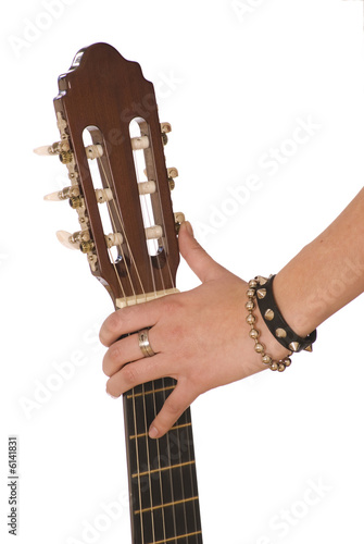 The top of the guitar holding by girls hand.