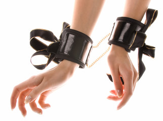 Leather handcuffs with golden chains on isolated background