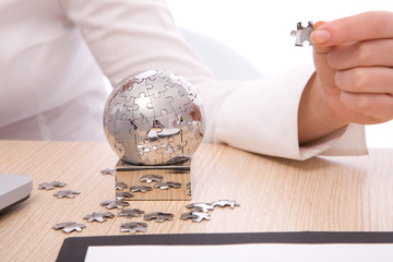 business concept with mini globe puzzle, shallow dof