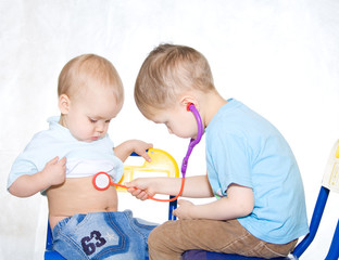 Two kids playing doctor. White window background