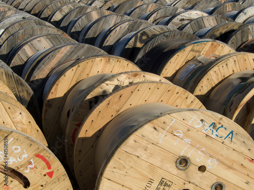 wooden spools of wire in the yard of a electric utility company