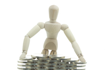 Manikin standing behind the coins wall