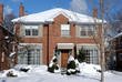 snow covered red brick house on sunny day