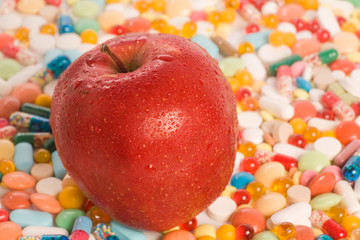 Conceptual photo of red apple with tablets on a background
