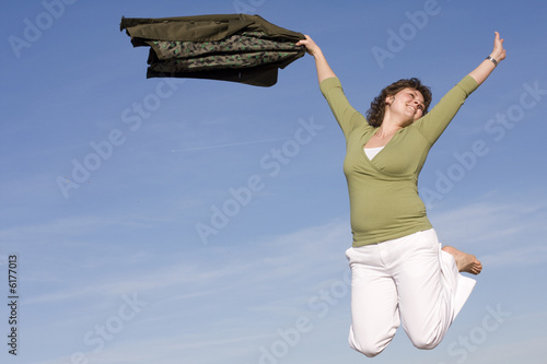 woman jumping in the sky, happy because spring is coming