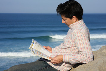 Young man reading a book with a great view over the sea