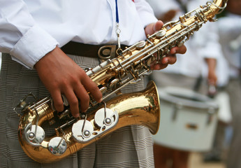 A saxaphone player marching in a parade