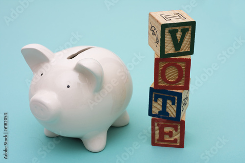Piggy bank with alphabet blocks spelling vote